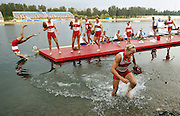 Canada's Adam Kreek walks out of the water with his gold medal as his teammates celebrate after the men's eight rowing competition at the Beijing 2008 Olympic Games, August 17, 2008.   REUTERS/Shaun Best   (CHINA)