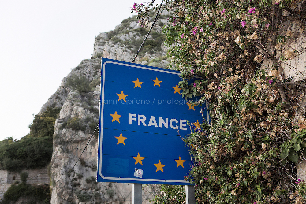 VENTIMIGLIA, ITALY - 17 NOVEMBER 2014:  A France road sign at the border between Italy and France in Ventimiglia, Italy, on November 16th 2014.<br /> <br /> The Ventimiglia-Menton border is the border between Italy and France crossed by migrants who decide to continue their journey up north towards countries such as Germany, Sweden, The Netherlands and the UK where the process to receive the refugee status or humanitarian protection is smoother and faster. in Ventimiglia, Italy, on November 17th 2014.