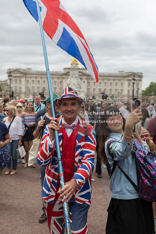 On the 100th anniversary of the Royal Air Force (RAF) and following a flypast of 100 aircraft formations representing Britain's air defence history which flew over central London, a patriotic man wearing a Union Jack suit and carrying a flag walks down the Mall, on 10th July 2018, in London, England.