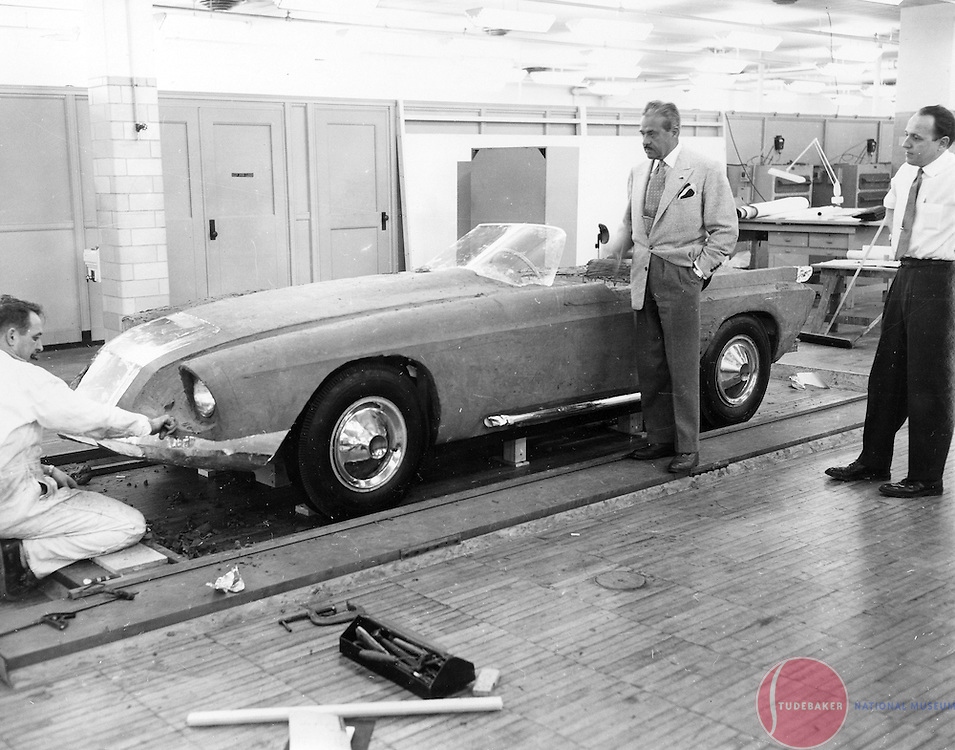 Raymond Loewy (center) and Robert Bourke (R) stand next to a clay model of Studebaker's aborted 1955 sports car.