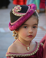A young girl is dressed for the annual Ronda Romantica festival in Ronda, Spain. The festival brings history alive as locals dress up as characters from the 18th and late 19th centuries. The event features a parade, music, food, dancing, and historical re-enactments.