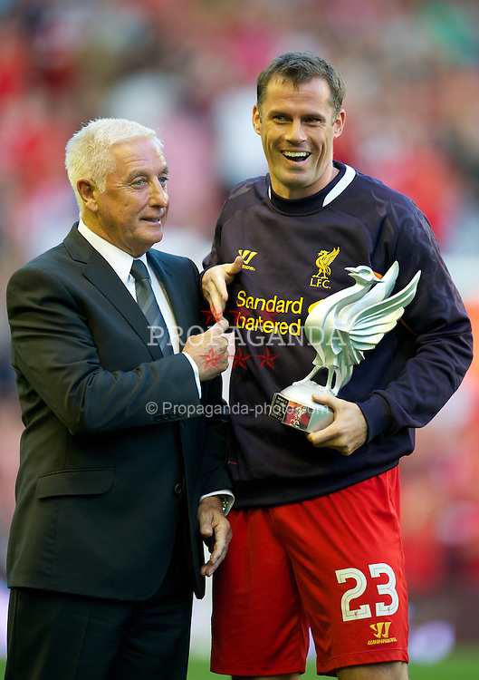 LIVERPOOL, ENGLAND - Thursday, August 9, 2012: Liverpool's Jamie Carragher receives an award from former manager Roy Evans to mark his achievement of making 700 appearances for the club, before the UEFA Europa League Third Qualifying Round 2nd Leg match against FC Gomel at Anfield. (Pic by David Rawcliffe/Propaganda)