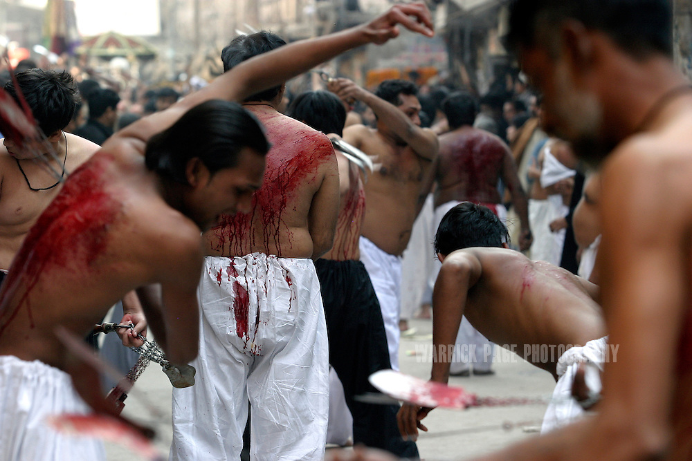 LAHORE, PAKISTAN - FEBRUARY 9: Dozens of men whip themselves with chains and blades during the Shia Muslim observance of Ashura, February 9, 2006, Lahore, Pakistan. Millions of Muslims worldwide observe Ashura during the month of Muharram to mourn the death of the Prophet Mohammed's grandson Immam Hussain. Some Shia participate in self-flagellation to punish themselves for failing to protect the prophet's  grandson. Many Shia, however, see this act as unnecessary. During the month of Muharram, many Shia's give generously to the poor and spend time in prayer. Security is stepped up every year throughout the country during Ashura due to ongoing violence between Shia and Sunni Muslim groups who frequently attack during opposing religious observances.  (Photo by Warrick Page)