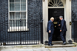 © Licensed to London News Pictures. 15/10/2019. LONDON, UK.  Boris Johnson, Prime Minister, and Jens Stoltenberg, NATO Secretary General, enter Number 10 Downing Street for talks.  Larry, Chief Mouser, (L) remains nonplussed.  Photo credit: Stephen Chung/LNP