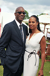 Athlete EDWIN MOSES andMICHELLE STRANIS at the Cartier Queen's Cup Polo Final, Guards Polo Club, Windsor Great Park, Berkshire, on 17th June 2012.