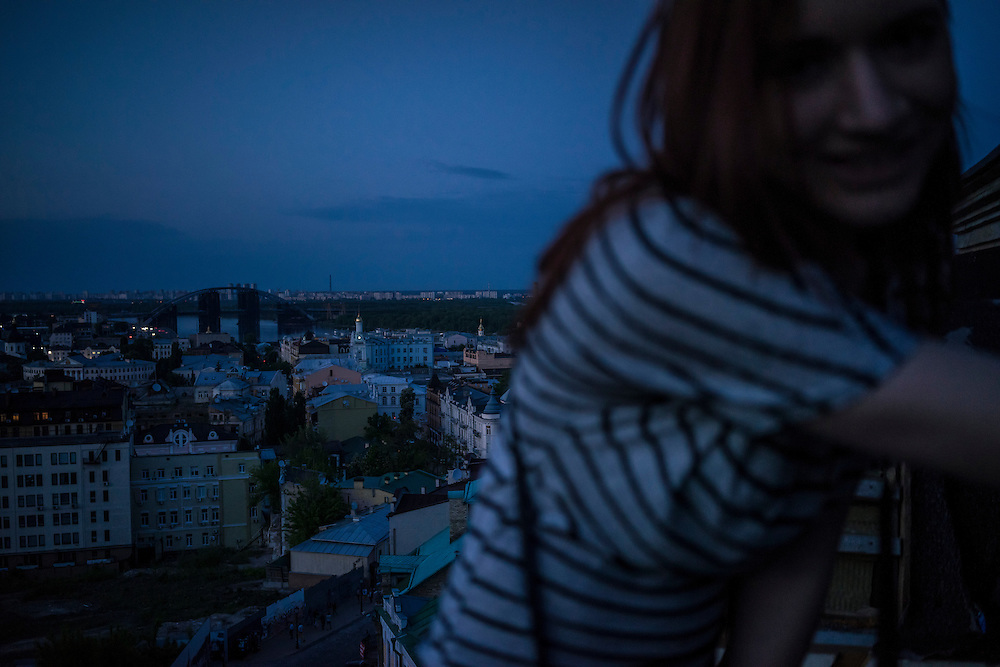 A woman climbs onto the roof of an abandoned apartment building under construction at sunset in the Podil neighborhood on Monday, May 11, 2015 in Kyiv, Ukraine.