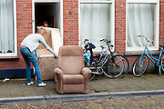 Twee studentes proberen een bank door de deur te krijgen.<br /> <br /> Two students are trying to put a couch as garbage out of their students home.