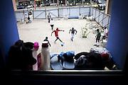 Alcuni migranti giocano a calcio nel cortile di ingresso delle ex palazzine olimpiche ti Torino. Poco oltre Via Giordano Bruno.