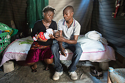 Cherline Pierre, 24, left, and her husband Clercy Wiilfrid, 25, holds their daughter at home in Port-au-Prince, Haiti, October 18, 2015. She was admitted to MSF's Centre de Référence en Urgence Obstétricale (CRUO) in Port-au-Prince due to her high blood pressure.