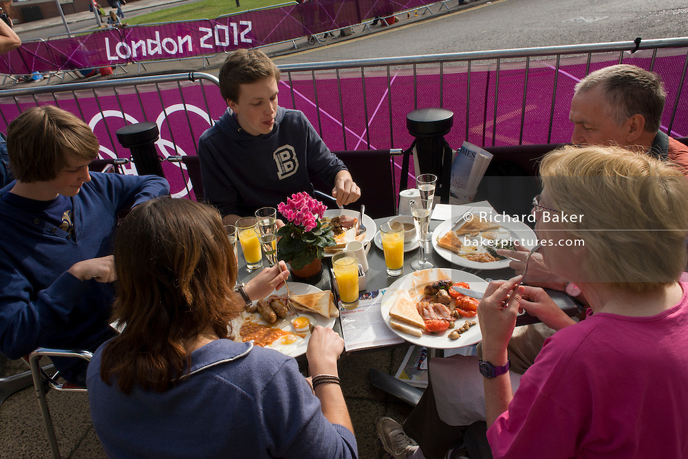 Spectators enjoy a full English breakfast on the first day of competition of the London 2012 Olympic 250km mens' road race. Starting from central London and passing the capital's famous landmarks before heading out into rural England to the gruelling Box Hill in the county of Surrey. Local southwest Londoners lined the route hoping for British favourite Mark Cavendish to win Team GB first medal but were eventually disappointed when Kazakhstan's Alexandre Vinokourov eventually won gold.