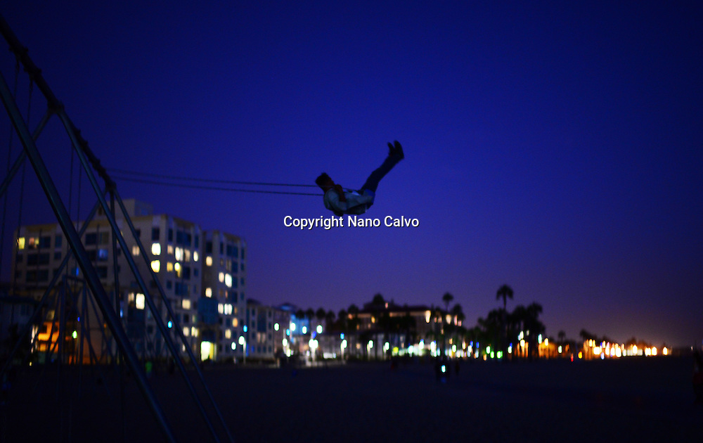 Young man playing with swing at night in Santa Monica beach, California.
