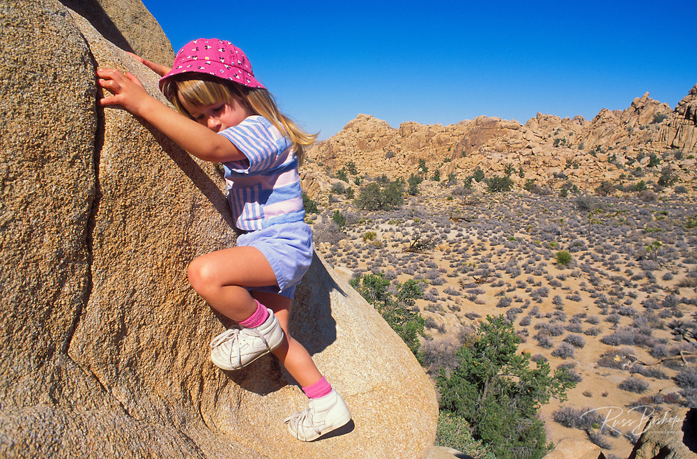 Child (age 3) climbing a granite boulder in Hidden Valley, Joshua Tree National Park, California