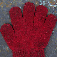 Grubby red woollen childs glove lying on rusty metal sheet