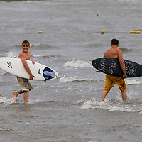 A pair of surfers head in to the waters  off the coast of Cedar Key, Florida hoping to catch some waves generated by Tropical Storm Alberto June12, 2006. REUTERS/Scott Audette