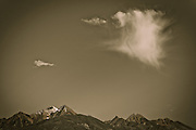 Wispy cloud formation above snow-capped mountain peaks of the Mission Mountains