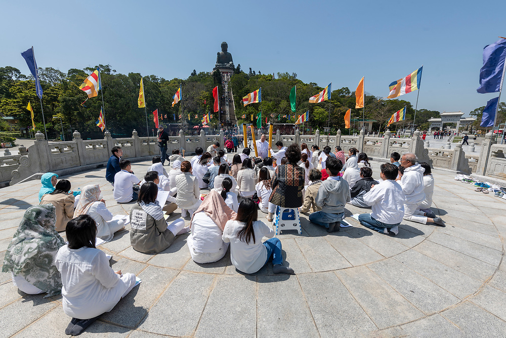 Young people vorship the Big Buddah at Lantau Island, Hong Kong, China.