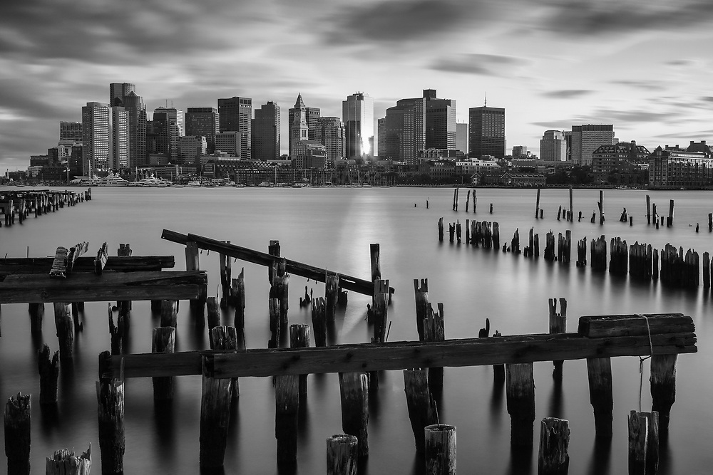 Scenic Boston Harbor skyline photography featuring landmarks such as the Marriott Hotel or Custom House of Boston and One International Place photographed on a magnificent sunset night. <br />