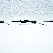 A Toyota FJ Cruiser windshield covered in snow in winter.