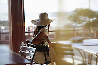 Woman in sunhat sits in transport cafe