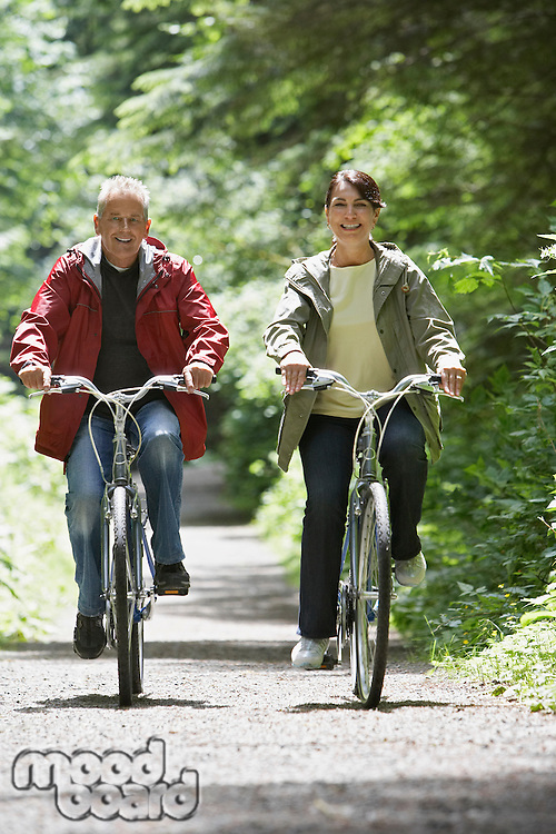 Senior man and middle-aged woman riding bicycles in forest front view