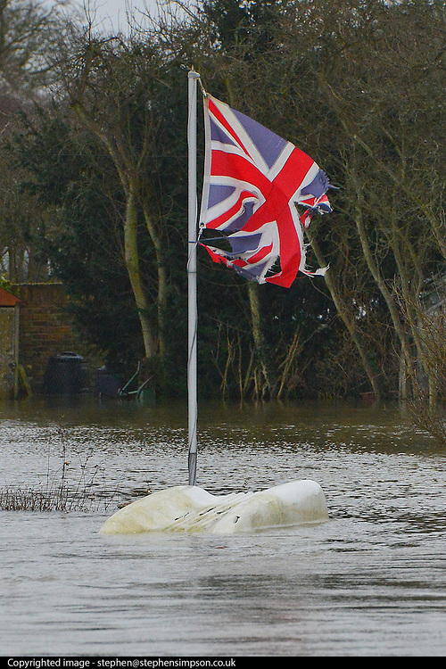 © Licensed to London News Pictures. 11/02/2014. Laleham, UK. A torn and tattered Union flag hangs above an overturned boat in floodwater.  Flooding in LALEHAM in Surrey today 11th February 2014 after the River Thames burst its banks. The Environment Agency has issued 14 Severe Flood Warnings alone the Thames. Photo credit : Stephen Simpson/LNP