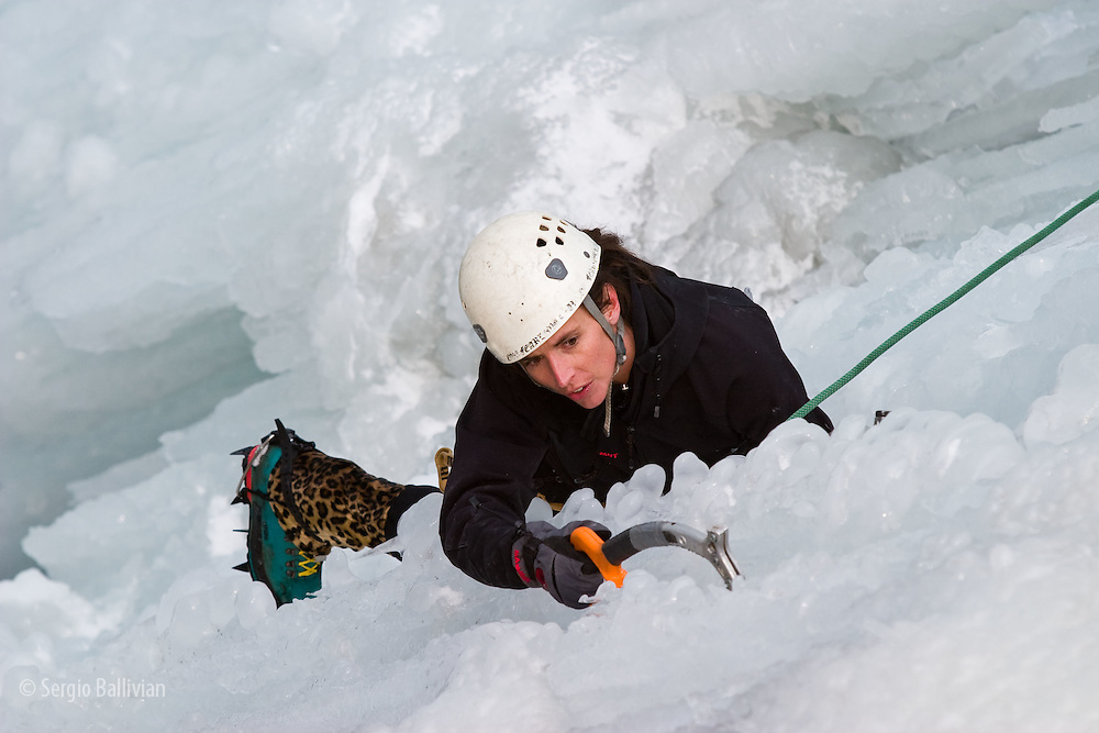 A female climbs a vertical column of ice in the Ouray Ice Park located in the city of Ouray, Colorado in the middle of winter.
