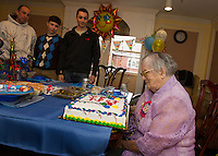 "Helen Clark ""Big Gram"" receives a birthday cake in honor of her 100th birthday with her grandson Scott Clark and great grand children Brady and Colby in the family room at Genesis Rehab in Laconia on Sunday afternoon.    (Karen Bobotas/for the Laconia Daily Sun)"