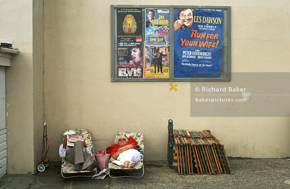 A holiday couple sleep on portable beds in a particularly shabby corner of Bournemouth, a seaside resort in southern England.