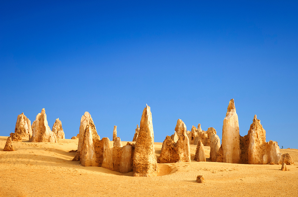 The Pinnacles in Western Australia. This is an area of natural limestone pillars rising above the yellow sand of the desert. They are formed by the acid leaching of the surrounding, weaker limestone which has left the more resiliant limestone standing above the desert.