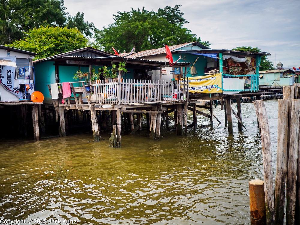 22 JULY 2015 - BANGKOK, THAILAND:  Housing along the Chao Phraya River south of the Krung Thon Bridge in Bangkok. This is one of the first parts of the riverbank that is scheduled to be redeveloped. The communities along the river don't know what's going to happen when the redevelopment starts. The Chao Phraya promenade is development project of parks, walkways and recreational areas on the Chao Phraya River between Pin Klao and Phra Nang Klao Bridges. The 14 kilometer long promenade will cost approximately 14 billion Baht (407 million US Dollars). The project involves the forced eviction of more than 200 communities of people who live along the river, a dozen riverfront  temples, several schools, and privately-owned piers on both sides of the Chao Phraya River. Construction is scheduled on the project is scheduled to start in early 2016. There has been very little public input on the planned redevelopment.           PHOTO BY JACK KURTZ