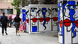 "© Licensed to London News Pictures. 04/08/2020. LONDON, UK.  People walk by Artist Anna Laurini's new artwork ""Urban Spinxes"".  Located outside a construction site just off Carnaby Street, the piece is  inspired by Pablo Picasso and Henri Matisse.  The construction company commissioned the artist to design something to cover up what would otherwise be bare wooden hoardings.  Photo credit: Stephen Chung/LNP"