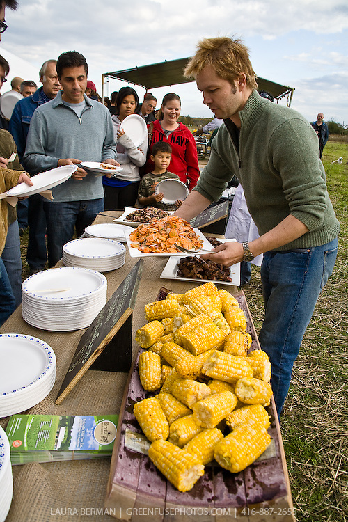 Guests lining up for food at an outdoor farm feast.