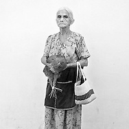 Old woman coming from the market in Suchitoto, El Salvador with a chicken in here hands
