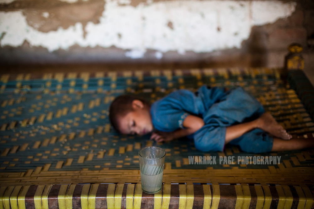 A glass of unclean water sits on the edge of a charpoy, in Noor Bano's home on October 13, 2011, in Manzoorabad, Pakistan. Noor's son, Mohammad Ali, 2, was discharged from the nutrition stabilisation centre in Jamsharoo, after being admitted two months ago with severe malnutrition brought on by TB and pneumonia. According to UN reports, hundreds of thousands of children in Pakistan suffer from severe-acute-malnutrition, with 15.1% of children experiencing acute malnutrition. Child malnutrition has breached emergency levels in Pakistan's Sindh province, after monsoon floods devastated the country's poorest region for a second year. Extreme poverty, poor diet and health, exposure to disease, and inadequate sanitation and hygiene annually produce alarming levels of malnutrition amongst children, but the floods have increasingly endangered an already vulnerable population. (Photo by Warrick Page)