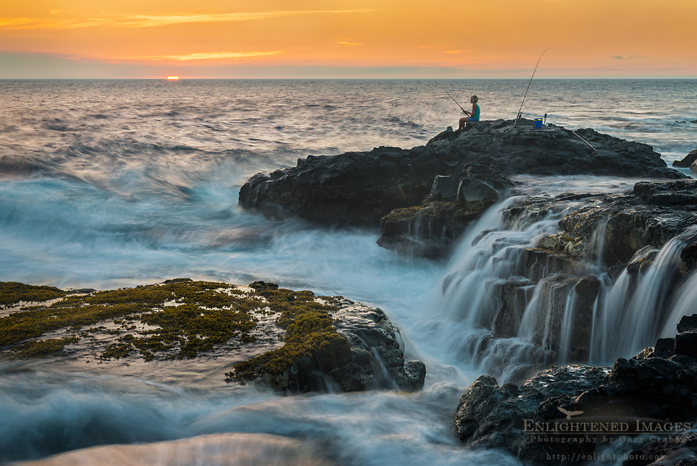 Young woman fishing from rocks at sunset near Kahili Point, Big Island of Hawai'i, Hawaii