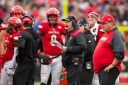 Louisville head coach Bobby Petrino, center works with quarterback Lamar Jackson to formulate the plan during a time out. The University of Louisville hosted Kentucky, Saturday, Nov. 26, 2016 at Papa John's Cardinal Stadium in Louisville. Kentucky won the game 41-38.