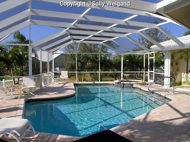 freeform pool; lanai; furniture; pool deck of pavers; screened cage; FL; Florida
