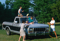 Man and three boys washing a pick up truck on a lawn in the country
