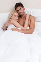 Portrait of young couple embracing in bed