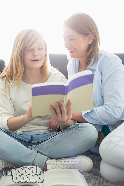 Mother assisting daughter in homework at home