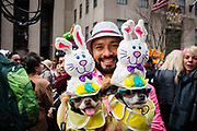 New York, NY - 21 April 2019. A man with two dogs dressed in rabbit-topped hats at the Easter Bonnet Parade and Festival on New York's Fifth Avenue.