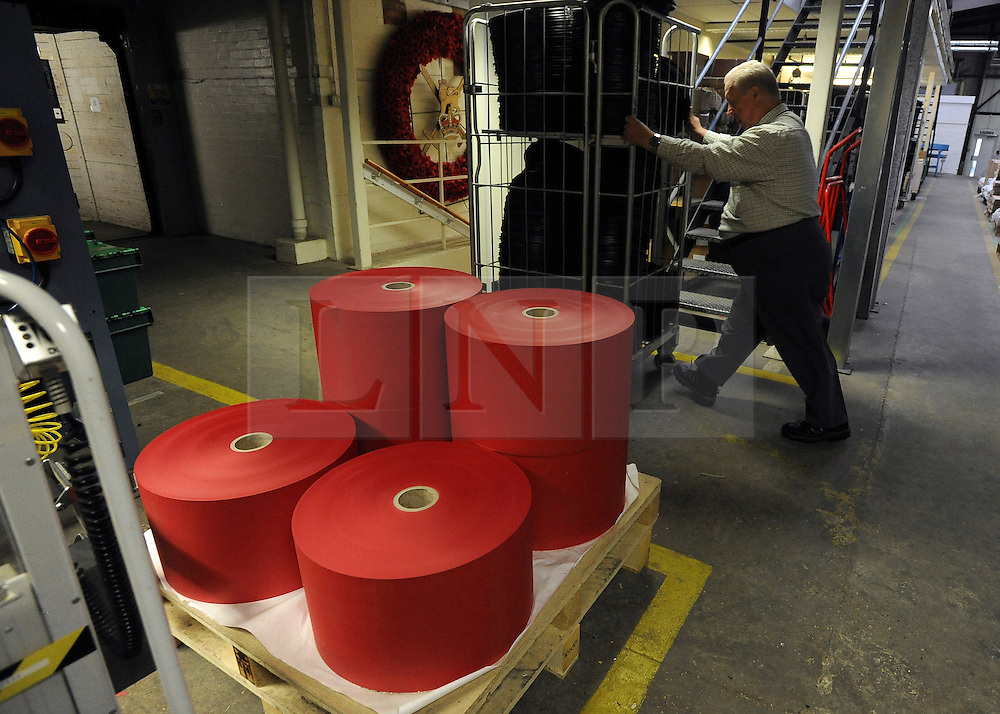 © Licensed to London News Pictures. 07/11/2011. Richmond, UK. A man pushes a cage of bases for wreathes past rolls of distinctive red paper that are used to make poppies. Red Poppies being made in The Poppy Factory in preparation for sale in 2012, Richmond, Surrey today 7th November.  The factory has been supplying the poppy, crosses and wreathes to the British Legion for almost 90 years. It is staffed by veterans, many whom of which are injured, sick or wounded of all ages. Photo credit : Stephen Simpson/LNP