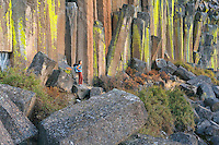Woman with backpack near basalt column cliffs in central Oregon USA.