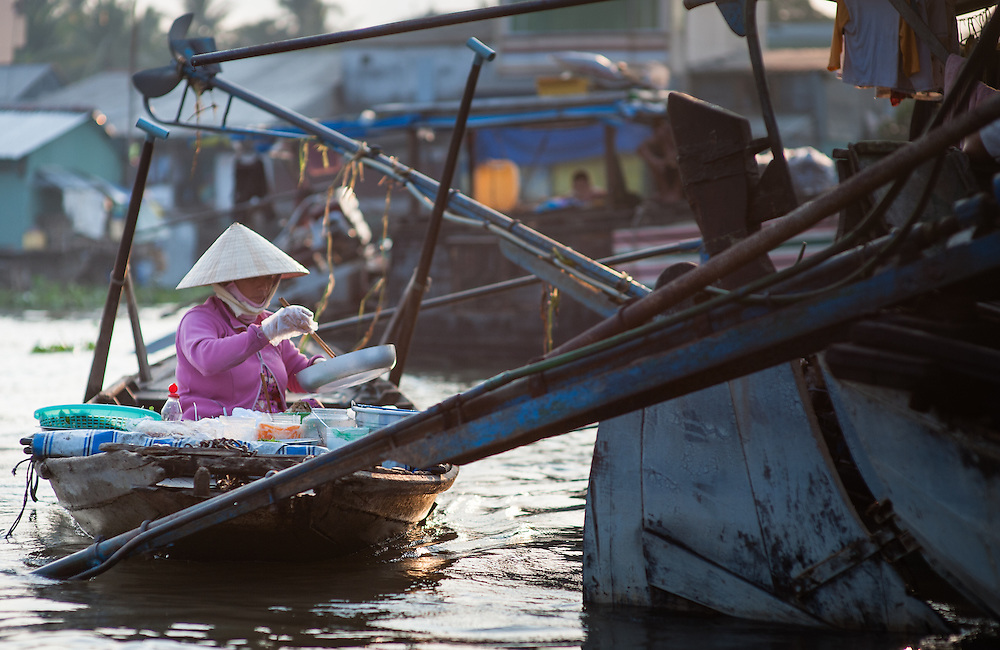 Woman on a restaurant boat serving food on the Mekong river (Vietnam)