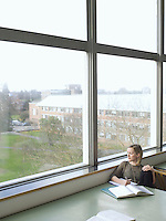 Young woman sitting in reading room by window