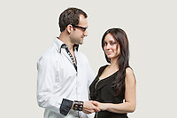 Young couple holding hands against gray background
