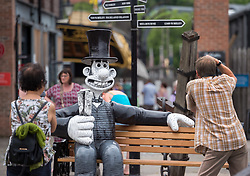 "© Licensed to London News Pictures.  01/07/2018; Bristol, UK. Gromit Unleashed 2. People take pictures of the ""Wallambard"" Wallace character (after Isambard Kingdom Brunel) installed outside the SS Great Britain at Bristol Harbourside for the Gromit Unleashed 2 sculpture trail. Gromit Unleashed 2 which officially begins on 02 July will see the Academy Award®-winning character Gromit by Nick Park at Aardman Animations returning to Bristol in 2018 for the second time on sculpture trails to raise money for  the Grand Appeal charity. The character of Gromit will be joined by Wallace and their arch nemesis Feathers McGraw. The trail will feature over 60 giant sculptures designed by high-profile artists, designers, innovators and local talent. Sculptures will be positioned in high footfall and iconic locations around Bristol and the surrounding area. Photo credit: Simon Chapman/LNP"