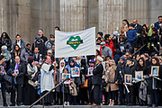 Relatives, friends and survivors leave led by a Grenfell heart banner and holding or wearing images of the victims - Grenfell Tower National Memorial Service at St Paul's Cathedral exactly six months on from the Grenfell Tower disaster. Grenfell Tower survivors and families of the bereaved attended and the order of service focused on remembering those who lost their lives, on providing messages of support for the bereaved, and on offering strength and hope for the future, for those of all faiths and none. London 14 December 2017