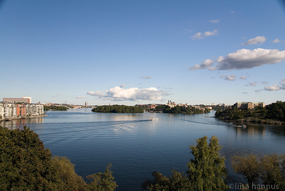A sightseeing boat travels the waters around the many islands that make up Stockholms skärgård (archipelago). This view from Stora Essingen shows the island of Lilla Essingen, Västerbron (the Western Bridge) and central Stockholm to the left, the islands of Långholmen and Södermalm in the centre, and Gröndal to the right.