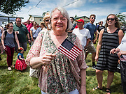 "04 JULY 2019 - INDIANOLA, IOWA: A woman with an American flag waits for Senator Kamala Harris (D-CA) before a campaign event in Indianola. Sen. Harris attended a ""house party"" in Indianola as a part of her campaign to be the Democratic nominee for the US presidency in 2020. Iowa traditionally holds the first selection of the presidential election cycle. The Iowa caucuses are Feb. 3, 2020.      PHOTO BY JACK KURTZ"
